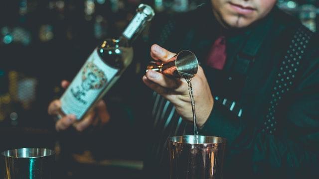 バーテンダーがお酒を注ぐ画像。