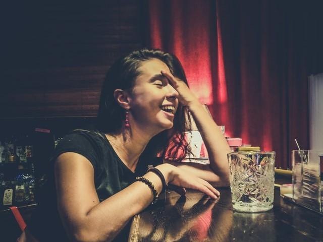 バーで笑う女性の画像。