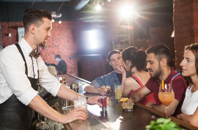 バーで客と話す風景の画像。