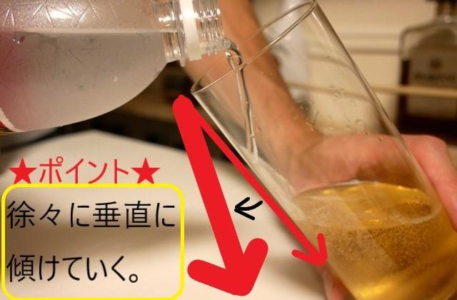 グラスを傾けながらウィスキーを注ぐ画像。