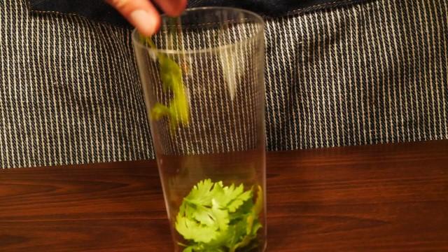 グラスにパクチーを入れる画像。