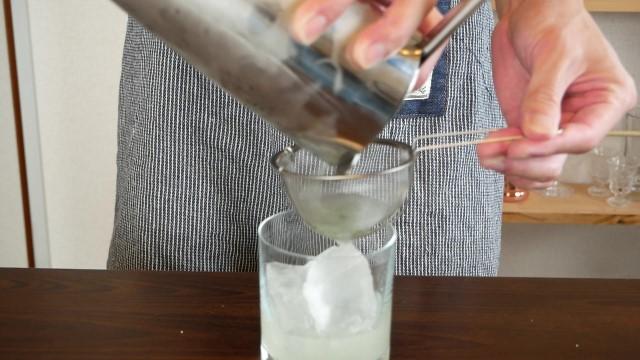 ジンバジルスマッシュをグラスに注ぐ画像。