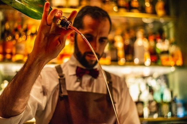 酒を注ぐバーテンダーの画像。