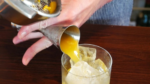 オレンジジュースを注ぐ画像。